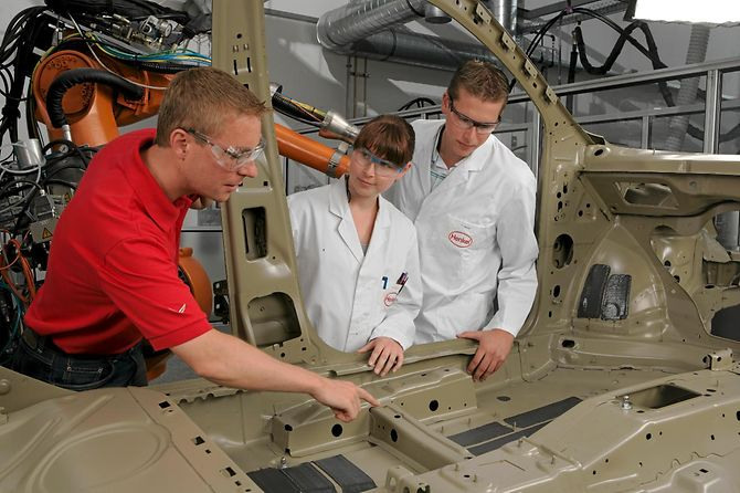 Henkel employees working on lightweight automotive components.